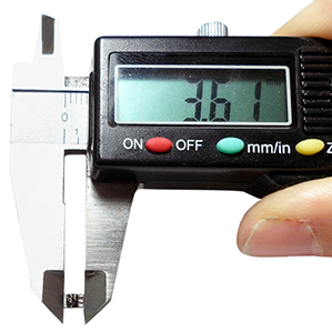 "Photo of a video camera being held by a micrometer. It measures 3.67 mm. The manufacturer claims it is the ""World's Smallest Video Camera""."
